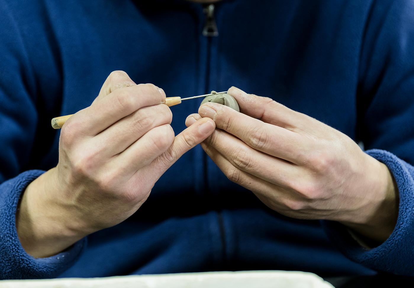 針などの道具で、胴体や顔の土の乱れを一つずつ直しながら整えています。